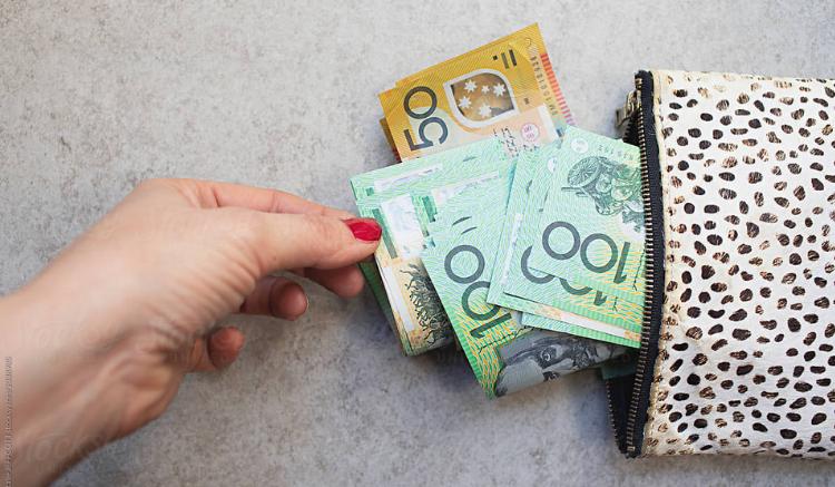 woman pulling australian currency from wallet