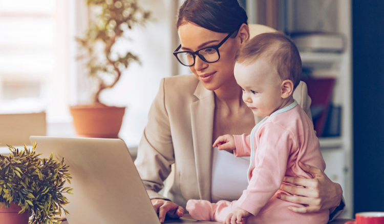 mom with glasses holding baby while they look at computer
