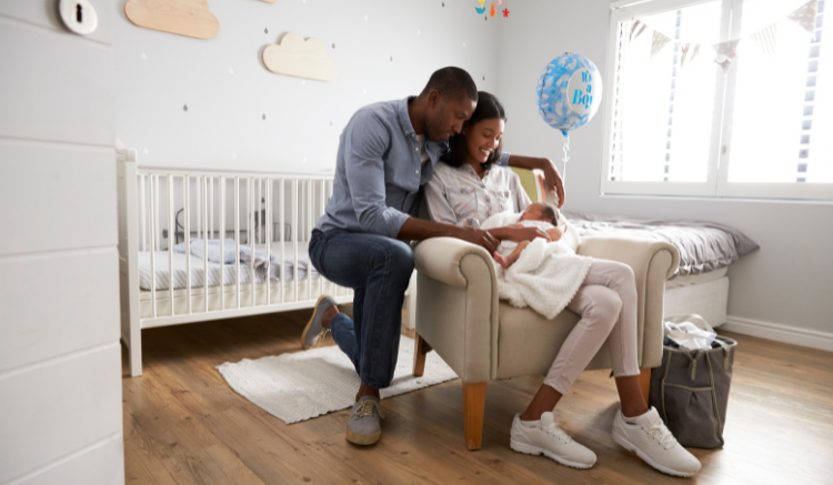 young couple holding infant baby boy in nursery room