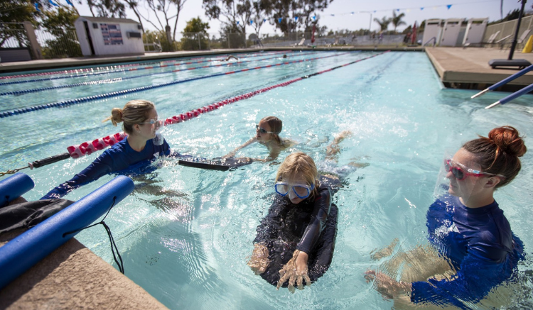 children swimming with ymca instructors in lap pool