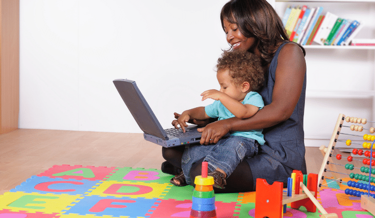 woman holding toddler on child's mat and working on computer