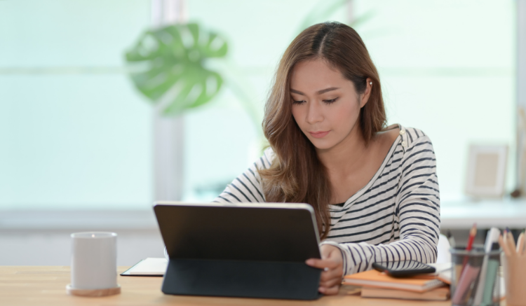 woman sitting at table, working on tablet device
