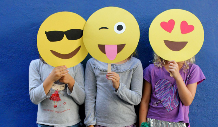 three young girls with paper emoji masks (from left to right: sunglasses emoji, tongue out emoji, and heart eyes emoji)