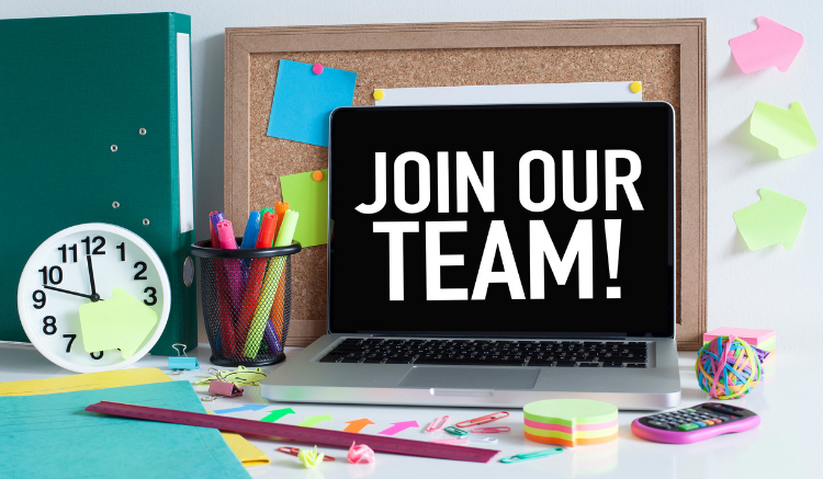 desk with colorful pens and sticky notes. laptop open and says 'join our team!'