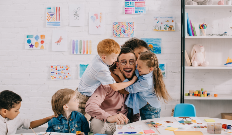 young male teacher with glasses being hugged by young students
