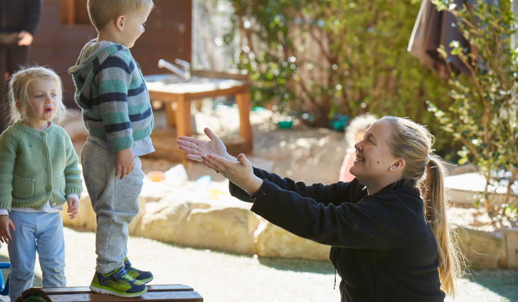 blonde woman reaching out her arms to hold little blonde boy