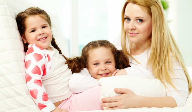 blonde mother smiling with two young brunette daughters