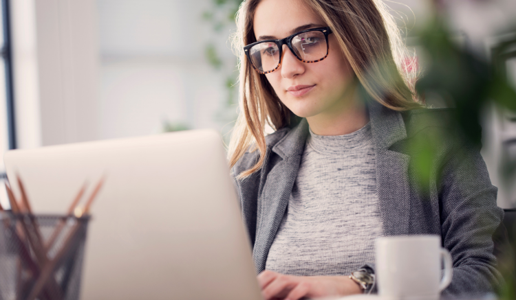 woman with glasses working on computer