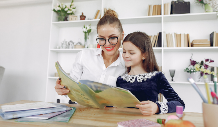 woman with glasses and hair bun reading with young girl