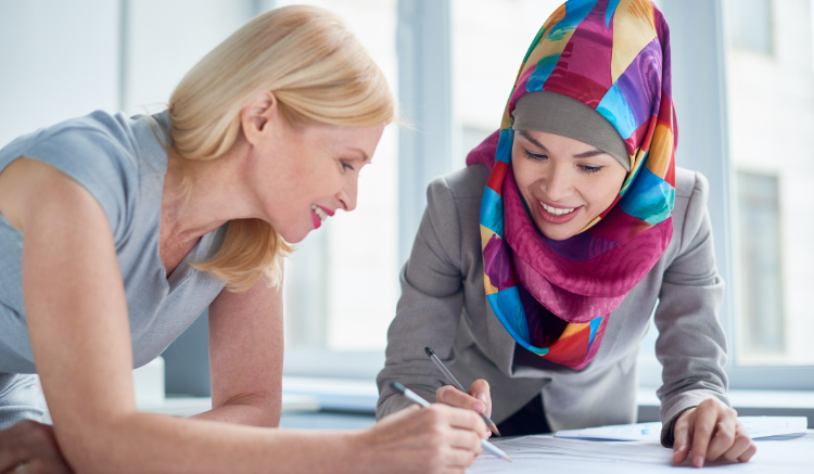 woman in colorful hijab working on papers with blonde woman