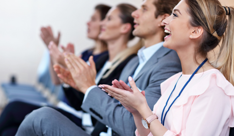 group of business people sitting in row and clapping