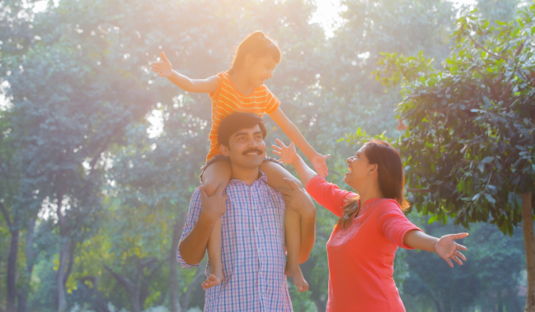 young daughter on father's shoulders while mom smiles and reaches towards her