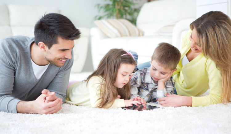 family of four with tow young children, all laying down as kids play on iPad