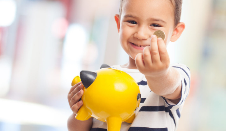 young boy holding piggy bank and coin